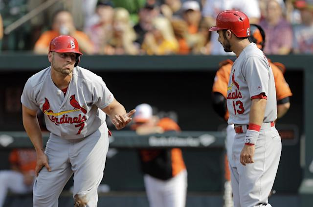 St. Louis Cardinals' Matt Holliday, left, reacts after he was tagged out and teammate Matt Carpenter (13) scored on a double by Jhonny Peralta in the first inning of an interleague baseball game against the Baltimore Orioles, Saturday, Aug. 9, 2014, in Baltimore. (AP Photo/Patrick Semansky)