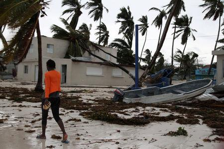 A woman walks among debris on the seashore in the aftermath of Hurricane Maria in Punta Cana, Dominican Republic, September 21, 2017. REUTERS/Ricardo Rojas