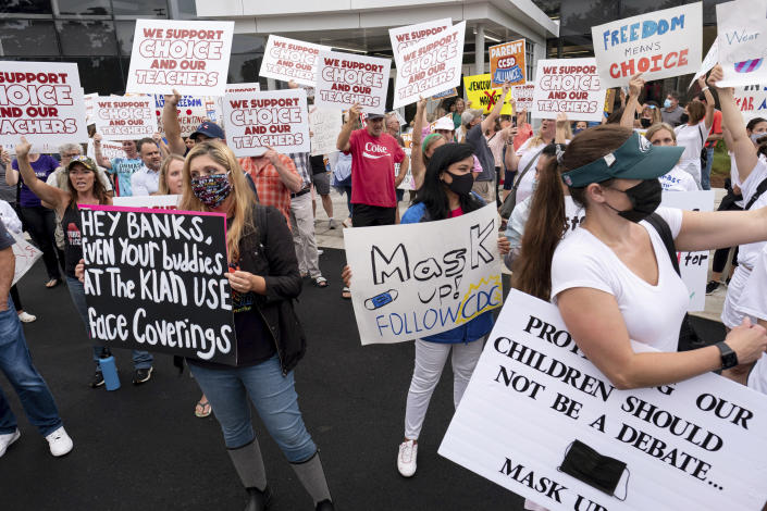 People in favor of and against a mask mandate for Cobb County schools gather and protest ahead of the school board meeting Thursday, Aug. 19, 2021, in Marietta, Ga. (Ben Gray/Atlanta Journal-Constitution via AP)
