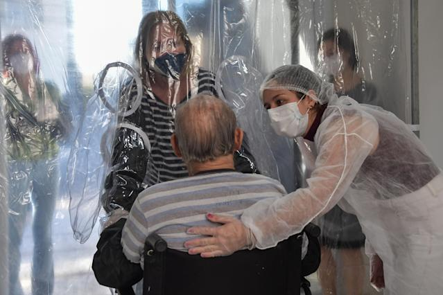Ana Lisboa (L) speaks with her 89-year-old father Raul Lisboa, through a transparent plastic curtain at a senior nursing home in Sao Paulo, Brazil, on June 13, 2020, amid the novel coronavirus (COVID-19) pandemic. (Photo by NELSON ALMEIDA / AFP) (Photo by NELSON ALMEIDA/AFP via Getty Images)