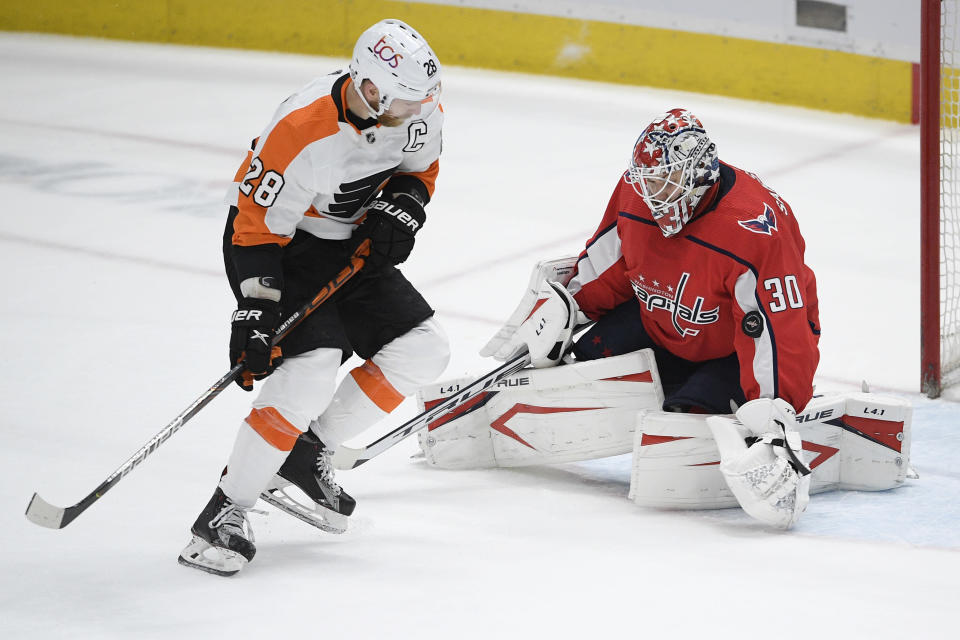 Washington Capitals goaltender Ilya Samsonov (30) stops the puck in front of Philadelphia Flyers center Claude Giroux (28) during the third period of an NHL hockey game Tuesday, April 13, 2021, in Washington. The Capitals won 6-1. (AP Photo/Nick Wass)