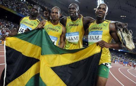 Men's 4x100m relay Asafa Powell, Usain Bolt, Michael Frater, Nesta Carter of Jamaica celebrate after winning the final of the athletics competition in the National Stadium during the Beijing 2008 Olympic Games August 22, 2008. Usain Bolt has lost one of his nine Olympic gold medals after Jamaica team mate Nesta Carter was found guilty of doping at the 2008 Beijing Olympics. REUTERS/Kai Pfaffenbach/File Photo