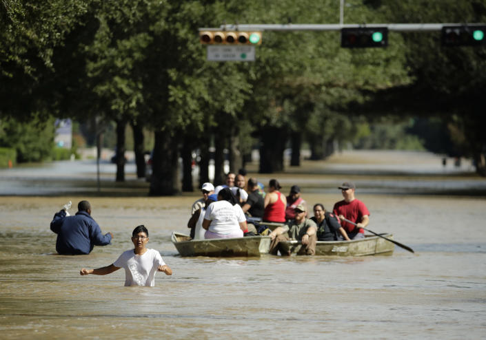 <em>People evacuate a neighborhood inundated after water was released from nearby Addicks Reservoir (AP)</em>