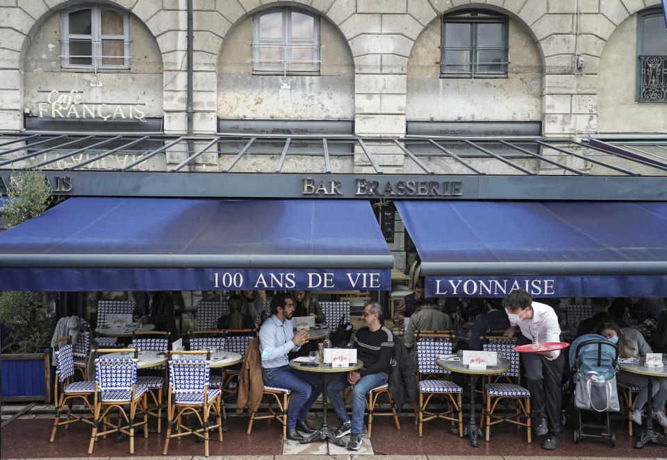 Customers sit at a cafe terrace in Lyon, central France, Wednesday, May, 19, 2021. It's a grand day for the French. Cafe and restaurant terraces are reopening Wednesday after a pandemic shutdown of more than six months deprived people of what feels like the essence of life in France. (AP Photo/Laurent Cipriani)