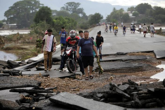 People walk among debris on a bridge over the Chamelecon river after the passage of Hurricane Eta, in Pimienta