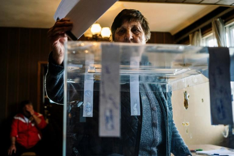 A woman casts her vote at a polling station during the country's parliamentary election in the village of Gabrovdol on March 26, 2017