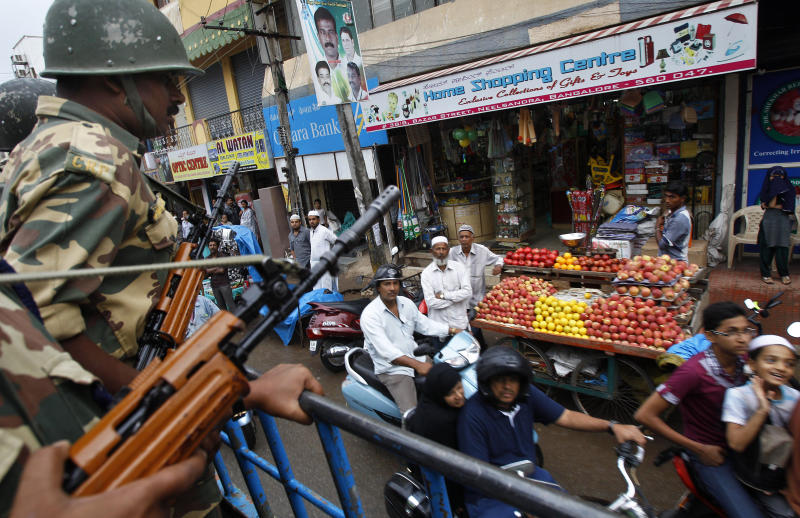 Indian paramilitary soldiers patrol the streets in Bangalore, India, Saturday, Aug. 18, 2012. Hundreds of Indians from the northeast are leaving the southern city of Bangalore and other towns, spurred by rumors they would be attacked in retaliation for communal violence in their home state of Assam. (AP Photo/Aijaz Rahi)