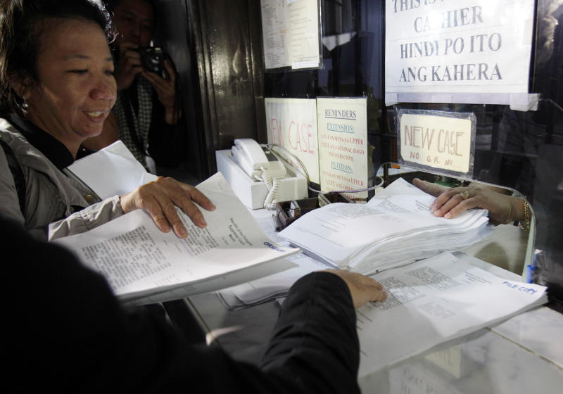 A Filipino journalist submits their groups' petition against the Cybercrime Prevention Act at the Supreme Court in Manila, Philippines on Wednesday, Oct. 3, 2012. Media groups and Filipinos stepped up calls Wednesday for repealing a tough new law that targets cybercrime but activists fear will be used to suppress online freedoms in the Southeast Asian nation. (AP Photo/Aaron Favila)