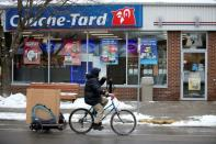 FILE PHOTO: A man cycles past a Couche-Tard convenience store in Montreal