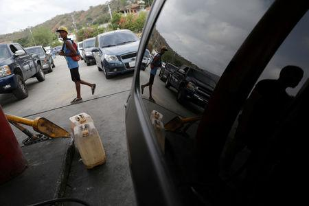 FILE PHOTO: A man walks past fuel containers while vehicle queue to refuel with gasoline in Puerto Cabello