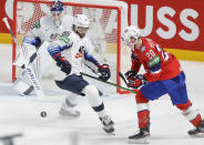 Christian Wolanin of the US, centre, challenges for the puck with Norway's Emilio Pettersen during the Ice Hockey World Championship group B match between Norway and United States at the Arena in Riga, Latvia, Saturday, May 29, 2021. (AP Photo/Sergei Grits)