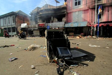 People ride motorbikes as they pass a building damaged after a riot in Jayapura, Papua