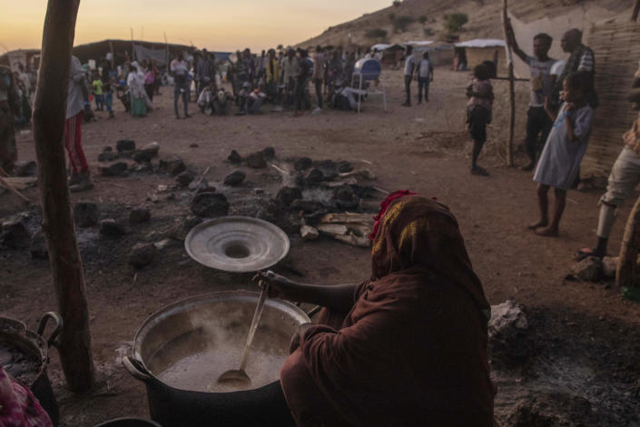 Sudanese women volunteer to cook for Tigray people who fled the conflict in Ethiopia's Tigray region, at Umm Rakouba refugee camp in Qadarif, eastern Sudan, Thursday, Nov. 26, 2020. Ethiopia's prime minister said Thursday the army has been ordered to move on the embattled Tigray regional capital after his 72-hour ultimatum ended for Tigray leaders to surrender, and he warned the city's half-million residents to stay indoors and disarm. (AP Photo/Nariman El-Mofty)