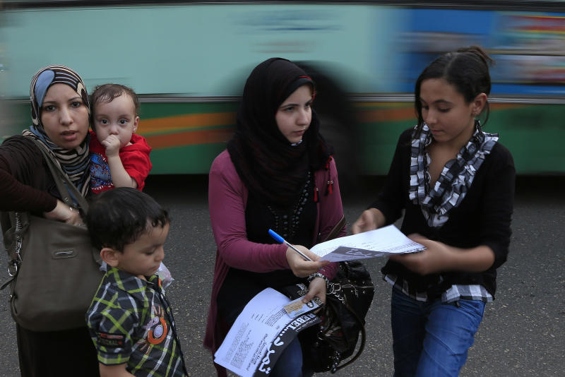 "In this Sunday, June 2, 2013 photo, an Egyptian woman signs a petition for Tamarod, Arabic for ""rebel"", a campaign calling for the ouster of Egyptian President Mohammed Morsi and for early presidential elections in the Shubra neighborhood in Cairo, Egypt. Young activists are trying to rally public discontent with Egypt's Islamist President Mohammed Morsi by fanning out in the streets and collecting millions of signatures on a petition calling for his removal. Morsi's Muslim Brotherhood has dismissed the campaign as irrelevant, even illegal, but the signature drive has stirred up Egypt's politics as the president nears the end of his tumultuous first year in office. (AP Photo/Hassan Ammar)"