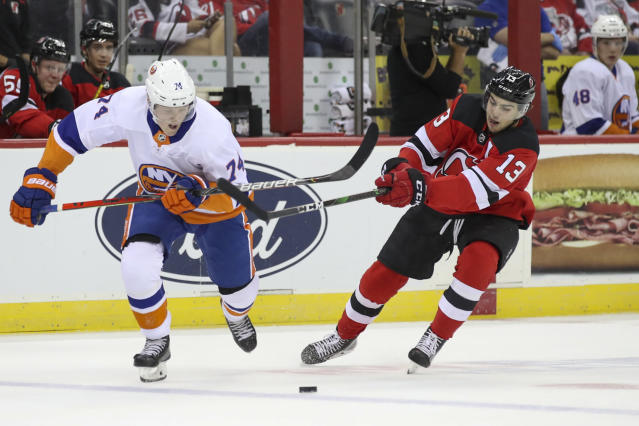 New Jersey Devils center Nico Hischier (13) and New York Islanders right wing Simon Holmstom (74) fight for the puck during the first period of a preseason NHL hockey game, Saturday, Sept. 21, 2019, in Newark, N.J. (AP Photo/Mary Altaffer)