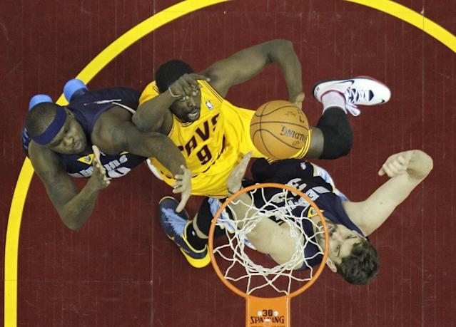 Cleveland Cavaliers' Luol Deng (9), from Sudan, shoots between Memphis Grizzlies' Zach Randolph, left, and Marc Gasol, from Spain, in the first half of an NBA basketball game on Sunday, Feb. 9, 2014, in Cleveland. (AP Photo/Mark Duncan)