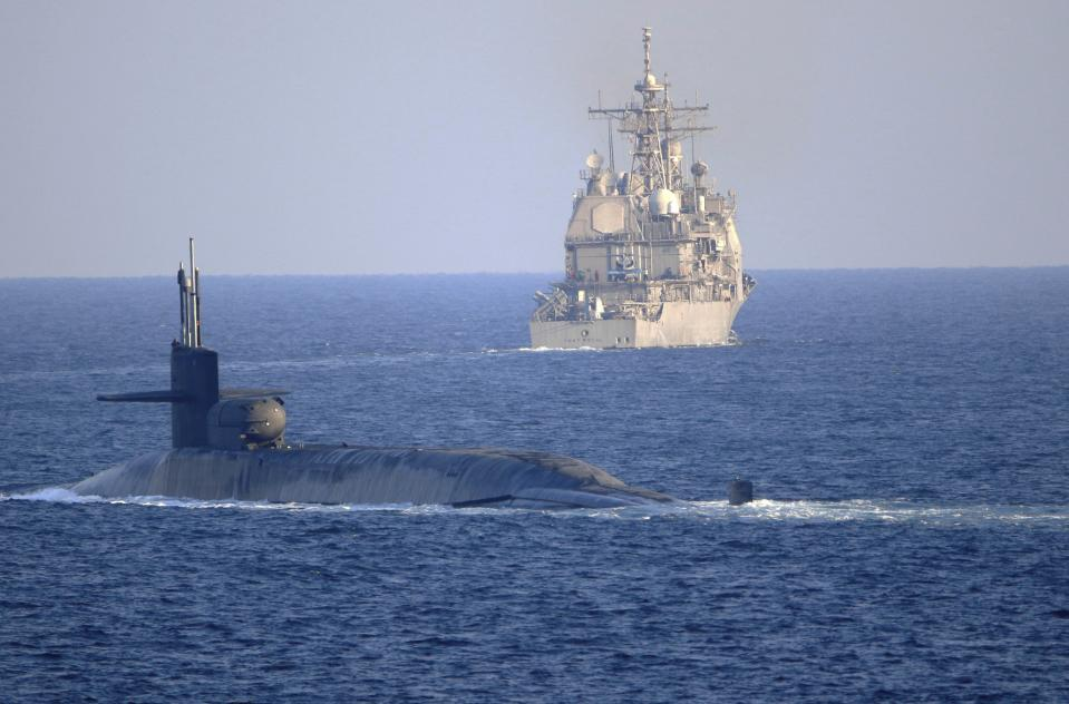 In this photo made available by the U.S. Navy, the guided-missile submarine USS Georgia, front, with the guided-missile cruiser USS Port Royal, transit the Strait of Hormuz in Persian Gulf, Monday, Dec. 21, 2020. The vessels traversed the strategically vital waterway between Iran and the Arabian Peninsula on Monday, the U.S. Navy said, a rare announcement that comes amid rising tensions with Iran. (Mass Communication Specialist 2nd Class Indra Beaufort/U.S. Navy via AP)