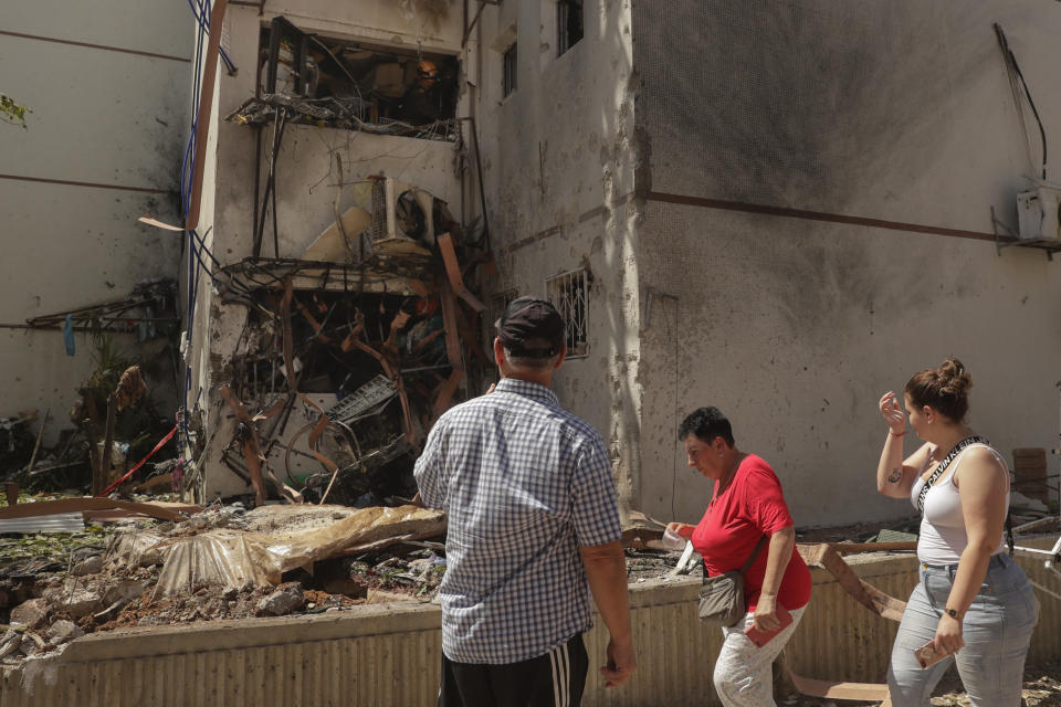 People look at a residential building after it was hit by a rocket fired from the Gaza Strip, in Ashdod, Israel, Monday, May 17, 2021. (AP Photo/Maya Alleruzzo)