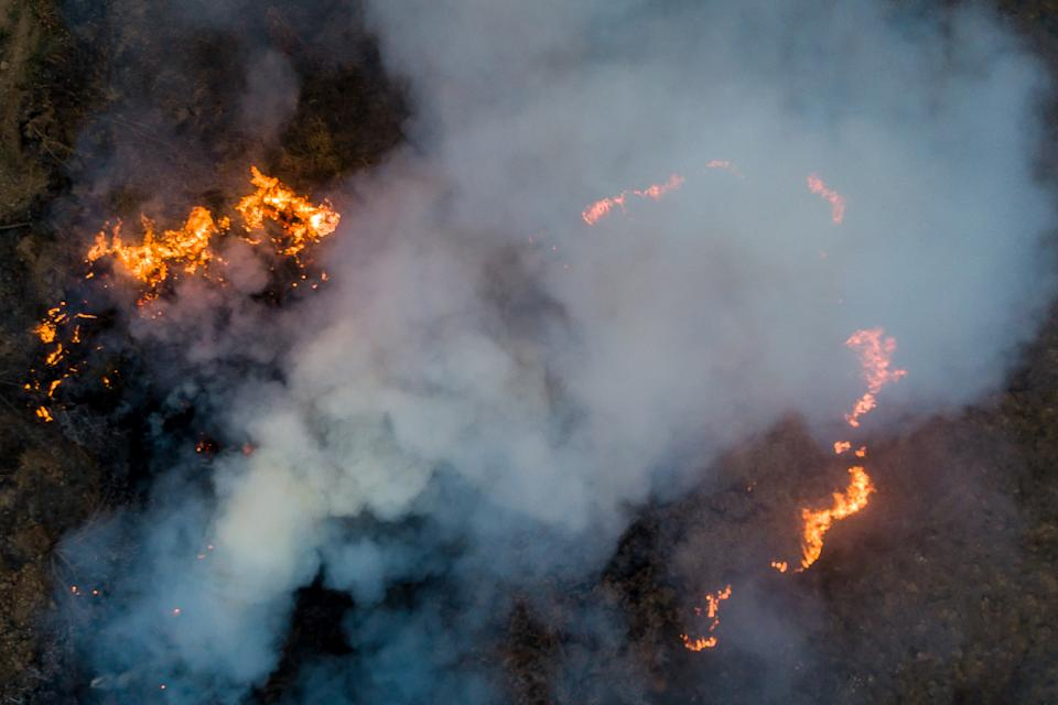 POCONE, BRAZIL - SEPTEMBER 25: An aerial view of a fire burning next to the Transpantaneira, a road that crosses the Pantanal on September 25, 2020 in Pocone, Brazil. Pantanal is located mostly within the Brazilian state of Mato Grosso and Mato Grosso do Sul and is the world's largest tropical wetland area, and the world's largest flooded grasslands. The region is considered by UNESCO as a World Natural Heritage and Biosphere Reserve. Since the beginning of September, more than 5,000 fires have been registered. The main cause of the induced fires is the livestock activity to transform the region into pastures. The biome has been going through four months of drought, which makes fire control difficult. The situation severely affects the local fauna and flora, which consists of thousands of species, some even endangered. (Photo by Buda Mendes/Getty Images)