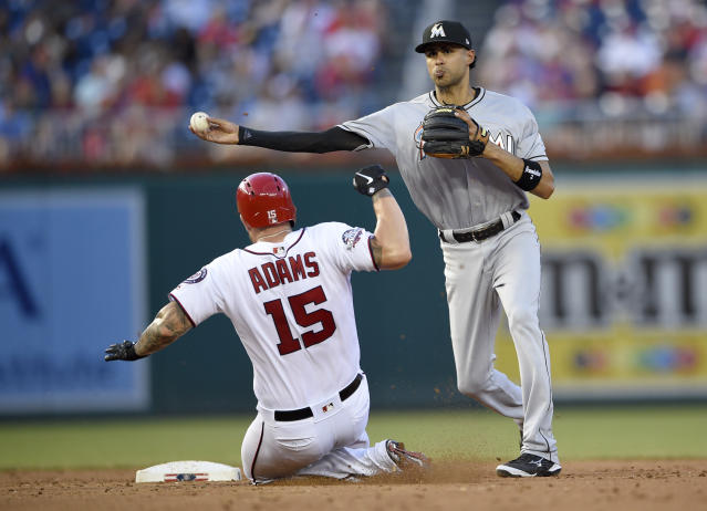 Washington Nationals' Matt Adams (15) is out at second as Miami Marlins shortstop Yadiel Rivera (2) throws to first to get Daniel Murphy to complete a double play during the second inning of a baseball game Thursday, July 5, 2018, in Washington. (AP Photo/Nick Wass)