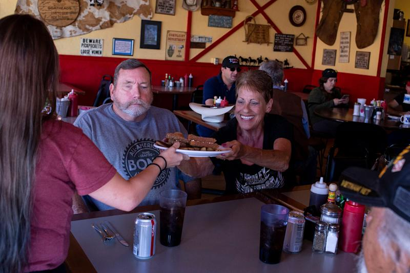 Leinani Jones hands food to Kathy Bondi on May 1, 2020, at Horseshoe Cafe in Wickenburg, Ariz.
