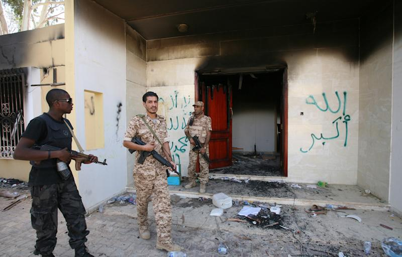 FILE - In this Sept. 14, 2012 file photo, Libyan military guards check one of the burnt out buildings at the U.S. Consulate in Benghazi, Libya, during a visit by Libyan President Mohammed el-Megarif to express sympathy for the death of American ambassador to Libya Chris Stevens and his colleagues in the Sept. 11, 2012 attack on the consulate. New Pentagon details show that the first U.S. military unit arrived in Libya more than 14 hours after the attack on the consulate in Benghazi was over and four Americans, including the ambassador, were dead. (AP Photo/Mohammad Hannon, File)
