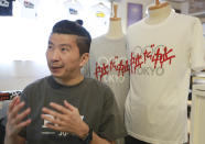 """Designer Susumu Kikutake speaks during an interview with the Associated Press in Tokyo, Wednesday, June 9, 2021. An online article showcasing his design calling for the Olympics to be cancelled resulted in harsh online comments, and he sold only around 10 shirts a month before the pandemic. But demand for the t-shirts has boomed in the past two months, with sales reaching 100 shirts in April and 250 in May. The characters on the shirt read """"Cancelation, Cancelation"""". (AP Photo/Koji Sasahara)"""