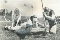 <p>A sports writer gets his physical fitness reading taken at a clinic set up by two volunteer college students.</p>