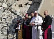 Pope Francis, surrounded by shells of destroyed churches, attends a prayer for the victims of war with Mosul and Aqra Archbishop Najib Mikhael Moussa, left, at Hosh al-Bieaa Church Square, in Mosul, Iraq, once the de-facto capital of IS, Sunday, March 7, 2021. The long 2014-2017 war to drive IS out left ransacked homes and charred or pulverized buildings around the north of Iraq, all sites Francis visited on Sunday. (AP Photo/Andrew Medichini)