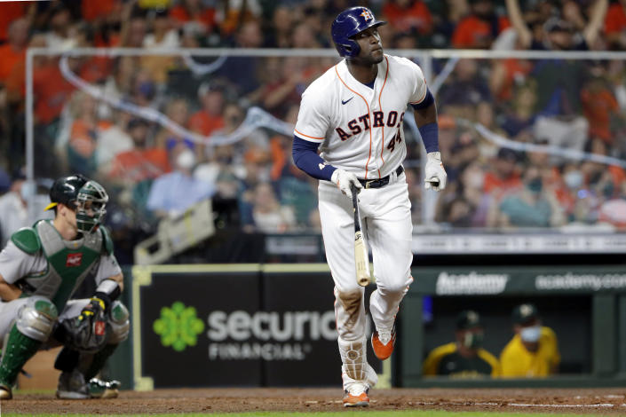 Houston Astros' Yordan Alvarez watches his home run as he heads to first base, next to Oakland Athletics catcher Sean Murphy during the sixth inning of a baseball game Thursday, April 8, 2021, in Houston. (AP Photo/Michael Wyke)