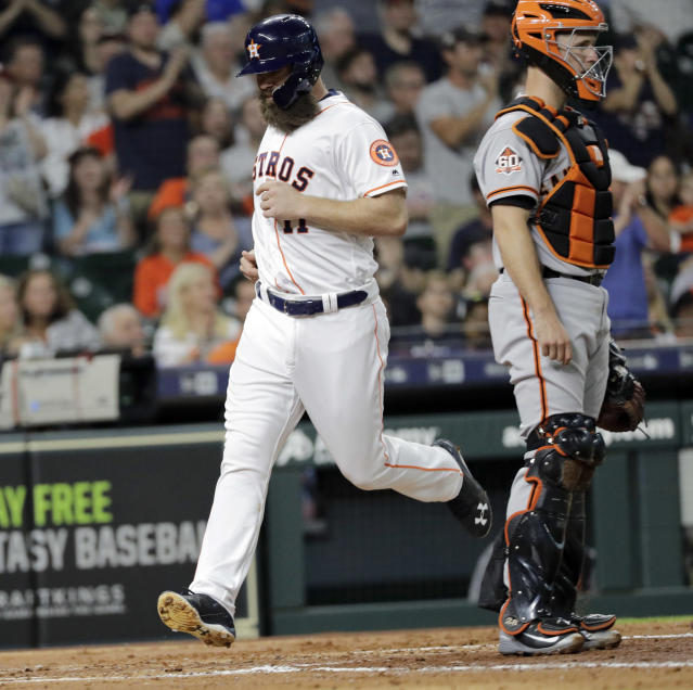 Houston Astros' Evan Gattis scores a run as San Francisco Giants catcher Buster Posey looks toward the field during the third inning of a baseball game Tuesday, May 22, 2018, in Houston. (AP Photo/David J. Phillip)