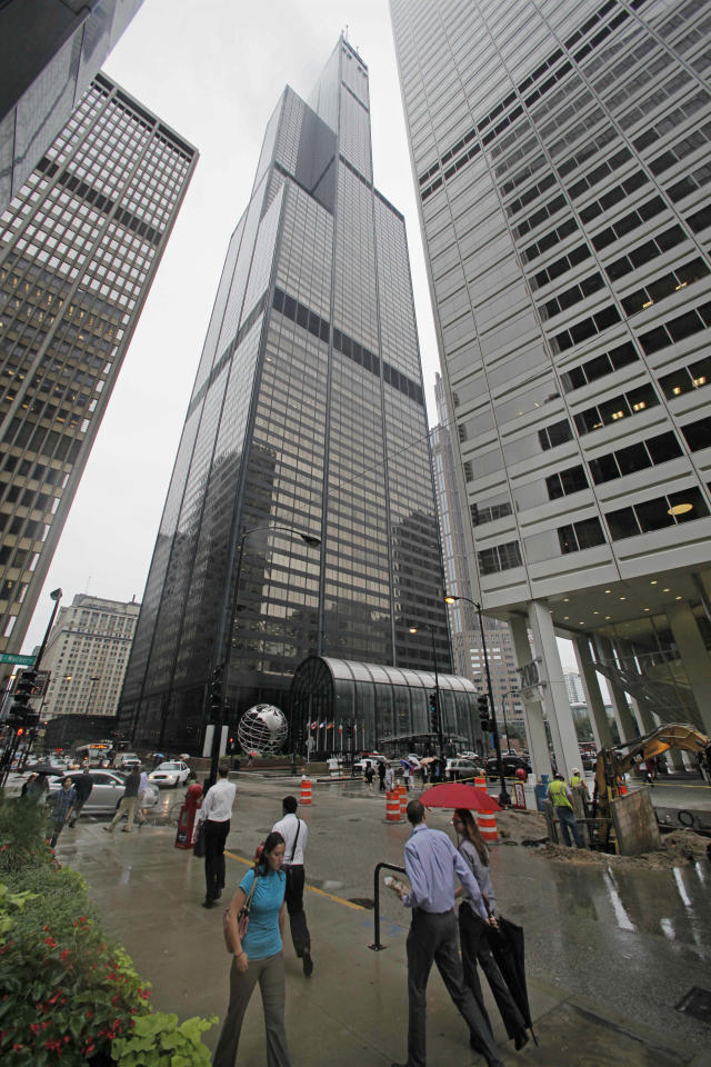 Pedestrians walk past the Willis Tower, Tuesday, Aug. 23, 2011, in Chicago. At Willis Tower, like other skyscrapers around the country, much has changed since two hijacked jets slammed into the twin towers of New York's World Trade Center a decade ago: Concrete barriers ring the outside of North America's tallest building, metal detectors greet visitors and sophisticated security cameras trace every movement in and around the structure. Experts say the obvious precautions still leave thousands of buildings vulnerable because the costs to retrofit existing structures may be too costly and cities and states may be slow to adopt newer, tougher building codes for new construction like those recommended after the deadliest terror attack on U.S. soil. (AP Photo/M. Spencer Green)
