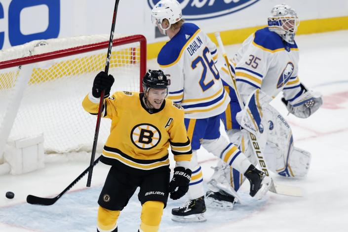Boston Bruins' Charlie Coyle (13) celebrates the goal by Matt Grzelcyk on Buffalo Sabres' Linus Ullmark (35) during the second period of an NHL hockey game, Saturday, March 27, 2021, in Boston. (AP Photo/Michael Dwyer)