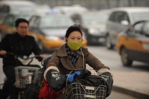A woman wears a mask as she rides a bicycle in Beijing in October 2011. Large jumps, measured from C02 emissions released into the atmosphere as a result of burning coal and gas, were visible in China, the United States and India, the world's top three polluters