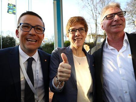 Annegret Kramp-Karrenbauer, State Minister-President and top candidate of the Christian Democratic Union Party (CDU), her husband Helmut (R) and Roland Theis of the CDU (L) reacts on first exit polls after the Saarland state elections in Saarbruecken, Germany, March 26, 2017.  REUTERS/Kai Pfaffenbach