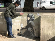 Calvin Benson, 48, puts a protective plastic sheeting over an artwork which appears to be by street artist Banksy. The environmental artwork has appeared near the Extinction Rebellion camp in Marble Arch, London.