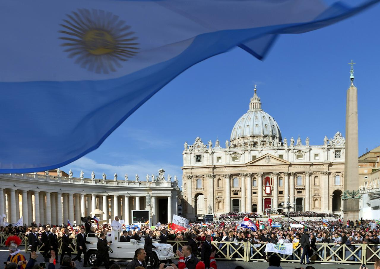 A flag from Argentina waves in the foreground as Pope Francis, bottom, is driven through the crowd prior to his inaugural Mass, in St. Peter's Square at the Vatican, Tuesday, March 19, 2013. Pope Francis thrilled tens of thousands of people on Tuesday gathered for his installation Mass, taking a long round-about through St. Peter's Square and getting out of his jeep to bless a disabled man in a wheelchair in the crowd. (AP Photo/Domenico Stinellis)