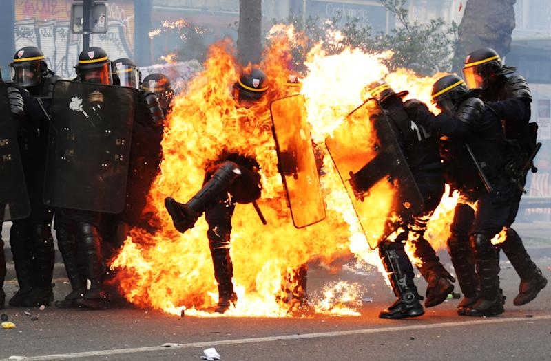 French CRS anti-riot police officers are engulfed in flames as they face protesters during a march for the annual May Day workers' rally in Paris on May 1, 2017. / AFP PHOTO / Zakaria ABDELKAFI