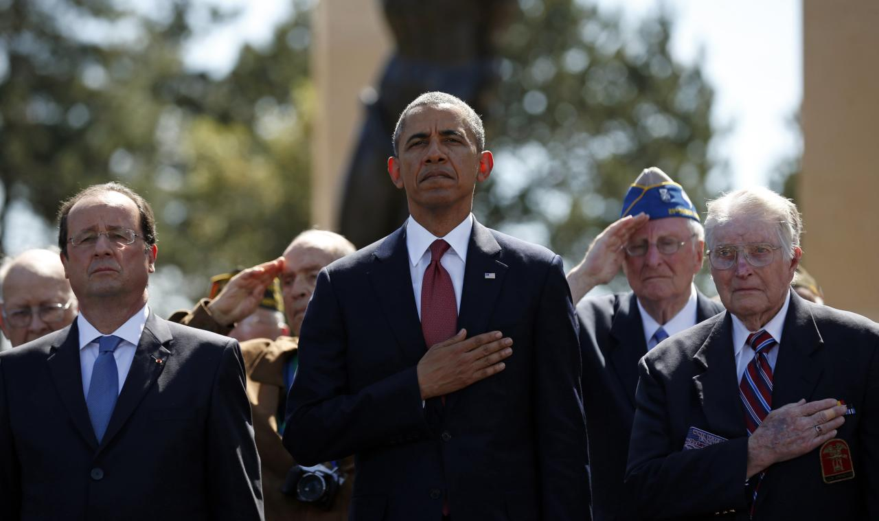 U.S. President Barack Obama (C) and French President Francois Hollande (L) stand with veterans as they participate in the 70th French-American Commemoration D-Day Ceremony at the Normandy American Cemetery and Memorial in Colleville-sur-Mer June 6, 2014. World leaders and veterans gathered by the beaches of Normandy under clear blue skies on Friday to mark the 70th anniversary of World War Two's D-Day landings, with host France hoping the event will help bring a thaw in the Ukraine crisis. REUTERS/Kevin Lamarque (FRANCE - Tags: POLITICS ANNIVERSARY CONFLICT)