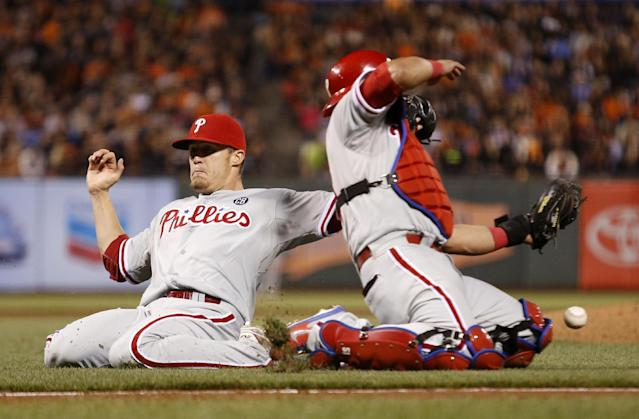 Philadelphia Phillies pitcher Ken Giles, left, and catcher Carlos Ruiz are unable to catch an infield fly ball hit by San Francisco Giants' Gregor Blanco during the eighth inning of a baseball game, Friday, Aug, 15, 2014, in San Francisco. (AP Photo/Beck Diefenbach)