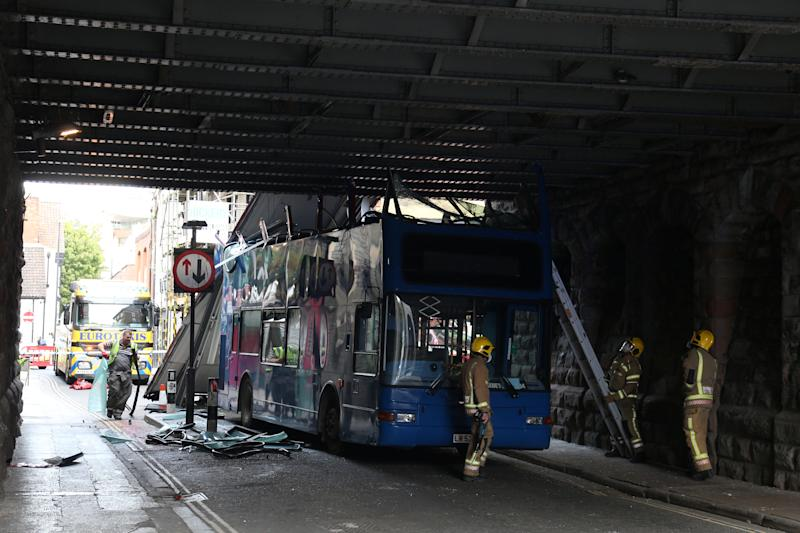 The scene in Bristol where a double decker school bus has driven under a low bridge and ripped its roof off. (SWNS)
