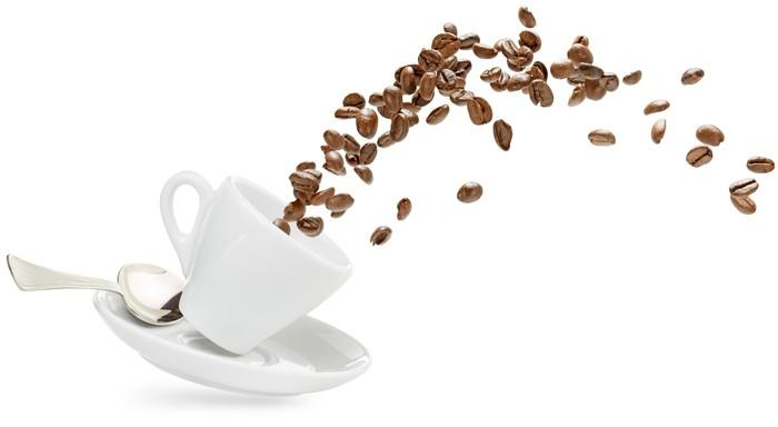 Coffee beans spilling out of a coffee cup.