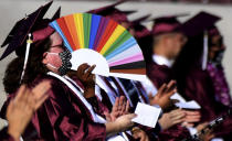 A student uses a colorful fan for shade on a hot day during the Mount Sac graduation at Hilmer Lodge Stadium in Walnut, Calif., Friday, June 11, 2021. (Keith Birmingham/The Orange County Register via AP)
