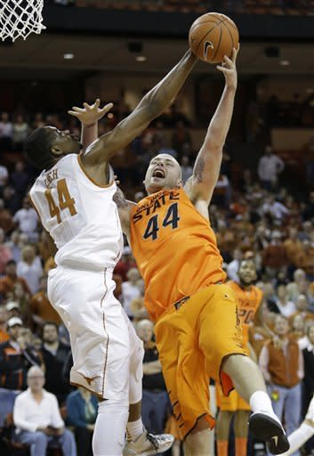 Texas' Prince Ibeh, left, and Oklahoma State's Philip Jurick, right, reach for a rebound during the first half of an NCAA college basketball game, Saturday, Feb. 9, 2013, in Austin, Texas. (AP Photo/Eric Gay)