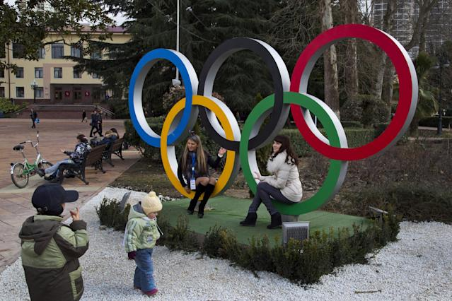 Russian women pose for snapshots next to Olympic rings in Sochi, Russia, Tuesday, Feb. 4, 2014. The opening ceremony for the 2014 Winter Olympics will be held on Feb. 7, and the competition will run until Feb. 23. (AP Photo/Bernat Armangue)