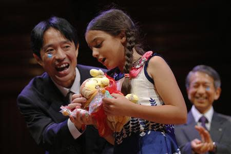 Muneaki Tomotake (L), of Japan, presents gifts to Miss Sweetie Poo, played by Sharanda Sundaram-Senders, as Tomotake and his colleagues accepted the 2013 chemistry prize during the 23rd First Annual Ig Nobel Prize ceremony at Harvard University in Cambridge, Massachusetts September 12, 2013. REUTERS/Brian Snyder