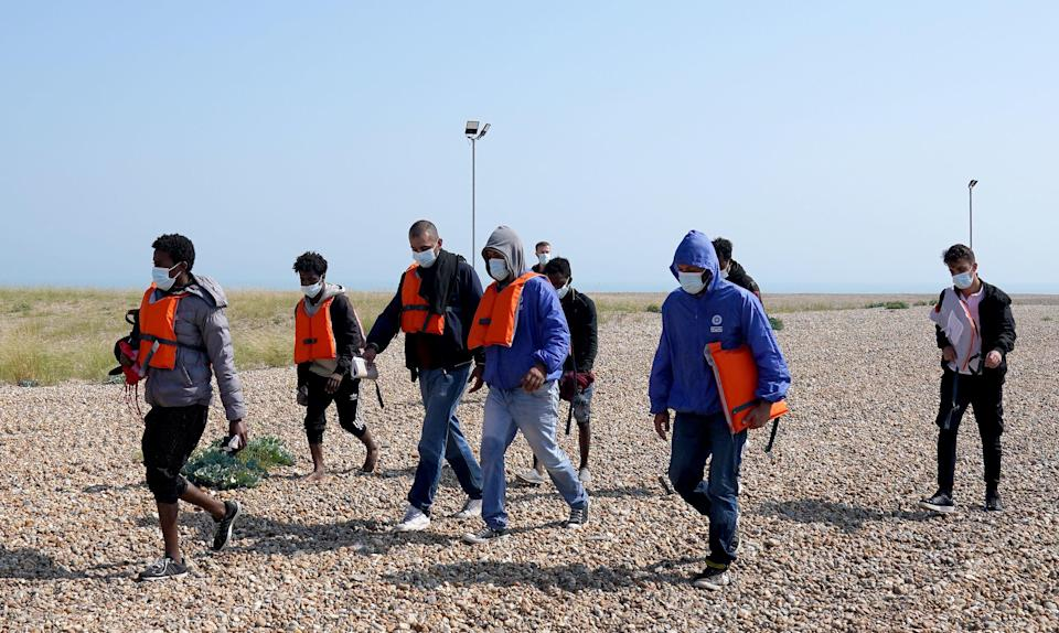 Migrants are escorted from the beach in Dungeness, Kent, by Border Force officers after landing on Tuesday morning (PA)