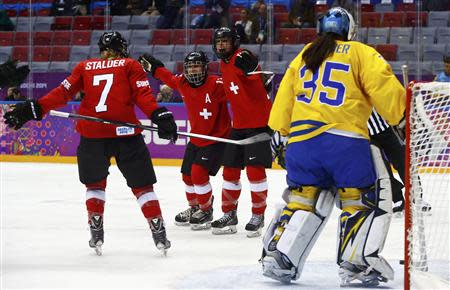 Switzerland's Jessica Lutz (R) celebrates her goal against Sweden's goalie Valentina Wallner (L) with teammates Sara Benz (13) and Lara Stalder (7) during the third period of their women's ice hockey bronze medal game at the Sochi 2014 Winter Olympic Games February 20, 2014. REUTERS/Mark Blinch