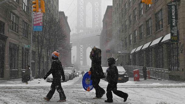 PHOTO: TOPSHOT - People walk through the snow in New York, on Feb. 18, 2021, after a snowstorm. (Angela Weiss/AFP via Getty Images)
