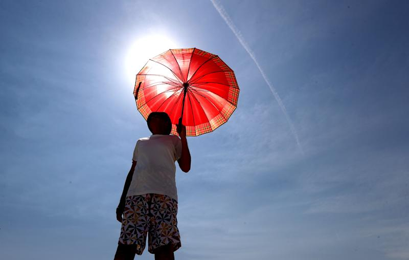 A man walks with an umbrella at Henley Beach during hot weather in Adelaide in November.